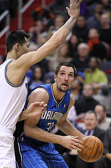 """A basketball player, wearing a blue jersey with the word """"ORLANDO"""" and the number 33 on the front, with the basketball and being guarded by a player who has his right arm extended."""