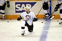 Photo de Ryan Whitney un genou sur la glace.