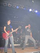 Band, wearing black t-shirts and jeans, plays during a performance.