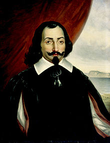 A half-length portrait of a man, set against a background that is a red curtain to the left and a landscape scene to the right. The man has medium-length dark hair, with a goatee and a wide mustache that is crooked up at the ends. He is wearing a white shirt with a wide collar, covered by a darker surcoat.