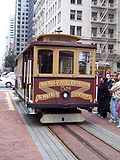 A cable car stopped next to people.