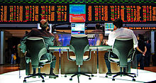 Two men sit at computer monitors with financial information