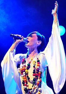 A woman singing into microphone, looking forward, left arm is raised in a white robe with a multicolor necklace.