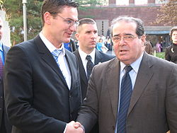 Scalia, wearing a beige jacket over shirt and tie, shakes hands with Jurij Toplak of European Election Law Association, while looking forward towards the camera.