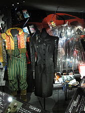 A photograph showing three costumes and some smaller items from the film. The left-hand costume is brightly coloured with striped trousers and an orange and yellow coat with a diamond pattern. The middle costume is a long black dress and the right-hand is a plastic see-through short coat.