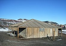 Wooden structure with door and two small windows. To the left is an open lean-to. In the background are partly snow-covered mountains.