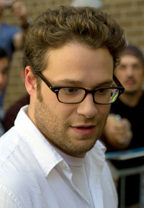 An image of a Caucasian man with brown, short, curly hair with a white buttoned shirt and black-framed glasses.