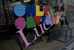 """A storefront window with a large slanted """"Luella"""" superimposed over a multi-coloured name logo that reads """"CHLOË SEVIGNY""""."""
