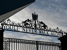 """Design of the top of a set of gates, with the sky visible. The inscription on the gates reads """"You&squot;ll Never Walk Alone""""."""