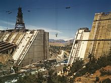 A crane lifts material used in the construction of a large concrete dam, which is still notched in the center to let the water flow through. Several pipes for future water conveyance use are visible on the left.