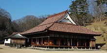 Wooden building with a hip-and-gable style roof and an open veranda surrounding the building.