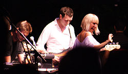 Upper body shot of three musicians performing. Left man is seen in right profile facing downwards and partly obscured by equipment. Second man is playing a guitar and is looking down. Furler is shown from behind, she is partly turned to her right, smiling and gesturing with her right arm. She is partly obscured by an audience member's silhouette.