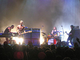 Four men are performing in front of an audience. The man at left is shown in right profile and is crouched over a keyboard with a second keyboard to his right. The second man is playing a guitar and singing into a microphone. The third man is seated behind a drum kit. The fourth man is shown in left profile playing a bass guitar. Two large speakers are behind the second man. Lights shine from the rear stage area.
