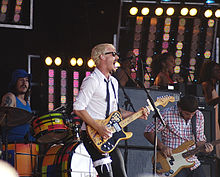Gillies at left behind his drum kit. Johns is singing wide-mouthed into a microphone and playing his guitar, he wears a garter with a ribbon over his pants on his right thigh. Joannou is playing his bass guitar. In the background are three female singers with one partly obscured at right.