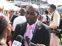 A bald black man in a suit, white shirt and pink tie, smiling and being interviewed by a female in glasses