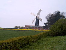 Beyond a foreground of green fields and low hedges is a tall, black cylindrical building with four white sails attached, set in a cruciform arrangement.