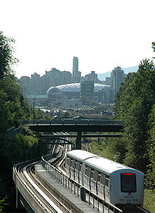 A two car train follows rail tracks under and bridge. In the background can be seen a domed sports stadium and high-rise buildings.