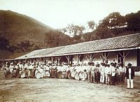 a large group of men, women and children holding agricultural implements and standing in front of a long, low building with hills rising in the background