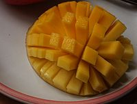 A halved, inside-out mango is cut in a grid pattern, still attached to the peel. The mango is inside-out, causing the resulting rectangles of fruit to splay out in a pattern similar to the tentacles of a sea urchin.
