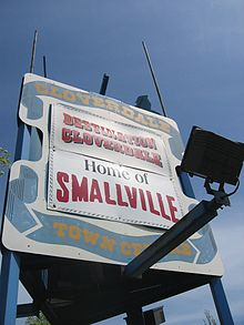 "A white billboard with blue ribbon painted around the edges. In the ribbon, the words ""Cloverdale Town Centre"" appear in yellow surrounding two bannders. The top banner reads, ""Destination Cloverdale"", while the bottom reads ""Home of Smallville""."