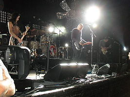 The Smashing Pumpkins perform on a brightly-lit stage with a large metal flower hanging over them. From left to right: Nicole Fiorentino, Mike Byrne, Billy Corgan, and Jeff Schroeder.