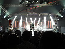 The Smashing Pumpkins perform on a back-lit stage dressed in white. From left to right: Ginger Pooley—a brunette Hispanic woman in her 20s wearing a sequined dress—looks at her bass guitar, Billy Corgan—a bald, middle-aged Caucasian man with a white jumpsuit and a black-and-white striped t-shirt—plays guitar, Jimmy Chamberlin plays a silver drum kit obscured behind Corgan, and Jeff Schroeder—a Korean male in his 30s with mid-length brunette hair—looks at his guitar while playing.