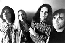 The Smashing Pumpkins pictured in a black-and-white promotional picture from 1990. All of them are in their mid-20s and face the camera. From left to right: James Iha is a Japanese man wearing a button-up floral print shirt, D'Arcy Wretzky is a Caucasian woman with blond hair wearing a jacket and necklace, Billy Corgan is a Caucasian male with long black hair and arms folded over his button-up shirt and necklace, and Jimmy Chamberlin is a Caucasian male with short black hair parted to the side wearing a black shirt.