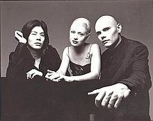 The Smashing Pumpkins in a black-and-white promotional photo from 1998, seated and looking at the camera. From left to right: James Iha is a Japanese man with shoulder-length black hair wearing a black suit, D'Arcy Wretzky is a Caucasian woman with blond hair pulled back wearing a black dress with thin straps and butterfly adornment on her left strap, and Billy Corgan is a Caucasian man with a shaved head wearing a black three-piece suit while gripping the table.