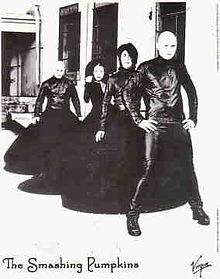 """The Smashing Pumpkins pose and face the camera for a promotional photo in 2000 wearing leather shirts with long black skirts. In front is Billy Corgan—a Caucasian male with a shaved head who is holding his hips and is wearing black leather pants rather than the skirts that the other musicians are wearing. Behind him is James Iha—a Japanese man with black hair parted to cover the left half of his face. Standing behind him is Melissa Auf der Maur—a Caucasian female with curly hair who is gripping her right shoulder. Finally, Jimmy Chambelin—a Cacuasian male—stands in the back. At the bottom of the photo are logos reading """"The Smashing Pumpkins"""" and """"Virgin""""."""