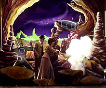 """The set from the """"Tonight, Tonight"""" music video features the performers dressed in Victorian clothing on a colorful set mimicking the moon. A moon monster is portrayed by a man at the right of the photo; he has on a pale green form-fitting jumpsuit with large blue and purple dots on it and wears matching make-up. On his head is a large prosthesis mimicking tall pale green hair. A man stands to the left wearing a suit and bowler and in front of him is a woman wearing a flowing gown who is lighting a rocket."""