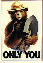 """Drawing of a grizzly bear with human features. He is wearing blue jeans with a belt and a brimmed hat with the name """"Smokey"""" on the cap, and has a shovel in his left hand. He is pointing to the viewer while the text """"Only You"""" is seen below him."""