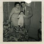 A woman and man, both in their thirties and both dressed in 'Sunday best', hold a similarly dressed very young girl standing on the arm of a floral-print sofa.