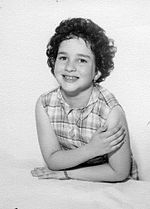 A studio pose of a six- or seven-year-old girl with short dark curly hair in a sleeveless print dress.