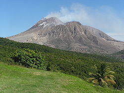 Large volcano rising above a tropical forest.