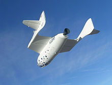 A white rocketship with oddly-shaped wings against a blue sky.