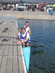 Photo of narrow kayak next to wooden dock. Two people sit in the kayak, each holding a paddle.
