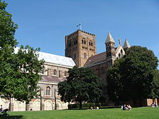 A long, low cathedral has a fine Norman brick crossing-tower rising in three stages of round-topped paired windows. The rest of the building is a conglomeration of styles in ancient brick, modern brick, ashlar and flint.