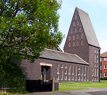 An angular taupe-coloured church on a bright sunny day. The church fills the image with the exception of a flat piece of green grass and grey pavement at the church's entrance and the dark green silhouette of trees along the left of the picture. The single-storey church has many small slitted triangular and rectangular windows across its façade, except for a dark rectangular entrance in which a man stands. At the far end of the church is a triangular spire standing tall and bold against a light blue sky at around six or seven times the height of a man.