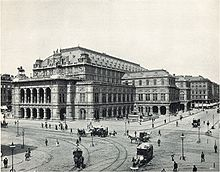 An imposing, heavily ornamented building in a city location, with numerous horsedrawn vehicles and pedestrians passing. There are visible tramlines in the street.