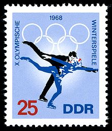 "A postage stamp with a blue background and two figure skaters skating, the date 1968 is centered on the top of the stamp along with the Olympic rings. The word ""Winterspiele"" is written down the right side, the words ""X Olympische"" are written down the left side. The number 25 is in the lower left corner and the letters ""DDR"" are in the lower right corner"