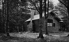 A cottage with a chimney stands in the woods.