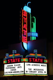 """Photograph of a large, elaborate neon sign at night. The word """"STATE"""" is written vertically in red neon tubing on a tower above a marquee. The marquee sign proper below the tower also has an elaborate neon tubing design, including the word """"STATE"""" written horizontally in red neon tubing above each of the two panels facing the camera. A reader board on the front-facing panel has black lettering that says """"AUBURN PLACER/PERFORMING ARTS/CENTER/LIVE FROM AUBURN.COM"""". A second reader board on a side panel says """"LIVE ACOUSTIC MUSIC//THE MITGARDS/IN CONCERT APRIL 26""""."""