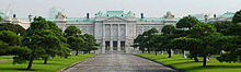 A large palace built of white stone in neo-baroque style. The facade is adorned with columns.