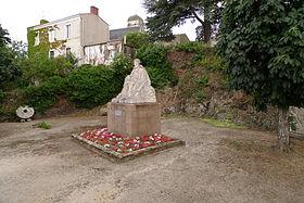 Statue de Joachim du Bellay, à l'arrière plan l'église