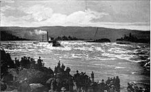 A river boat with more than a dozen windows along its visible side runs a set of rapids on a very large river. Smoke or steam rises from its smokestack and flows behind the boat parallel to the water. In the foreground, a crowd of 50 or people watch the boat from the rocky shore.