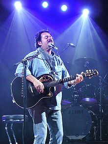 Lukather stands on stage, playing a black Ovation Adamas acoustic-electric guitar and singing into a microphone.