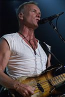 Man wearing a white cutoff shirt while singing into a microphone and playing a guitar.