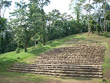 A large grassy mound with a wide stone stairway climbing from the bottom centre toward the summit at top right. The mound has scattered trees around the stairway with increasingly thick vegetation toward the far side of the structure.