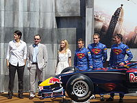 Brandon Routh, Kevin Spacey and Kate Bosworth alongside pilots Christian Klien, Robert Doornbos and David Coulthard, who wear racing overalls with the Superman insignia on the chest. In front of them is the Red Bull Racing racecar, which has the Superman insignia painted atop and sideways of the chassis.