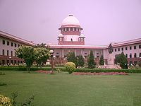 The Supreme Court of India with Green coloured lawn and the building which shows its entrance to the court